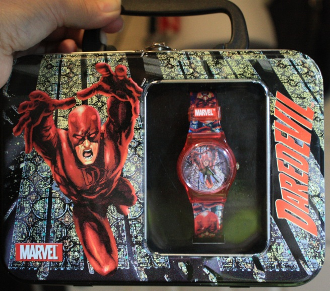 DD analog wristwatch in red in the lunchbox tin packaging