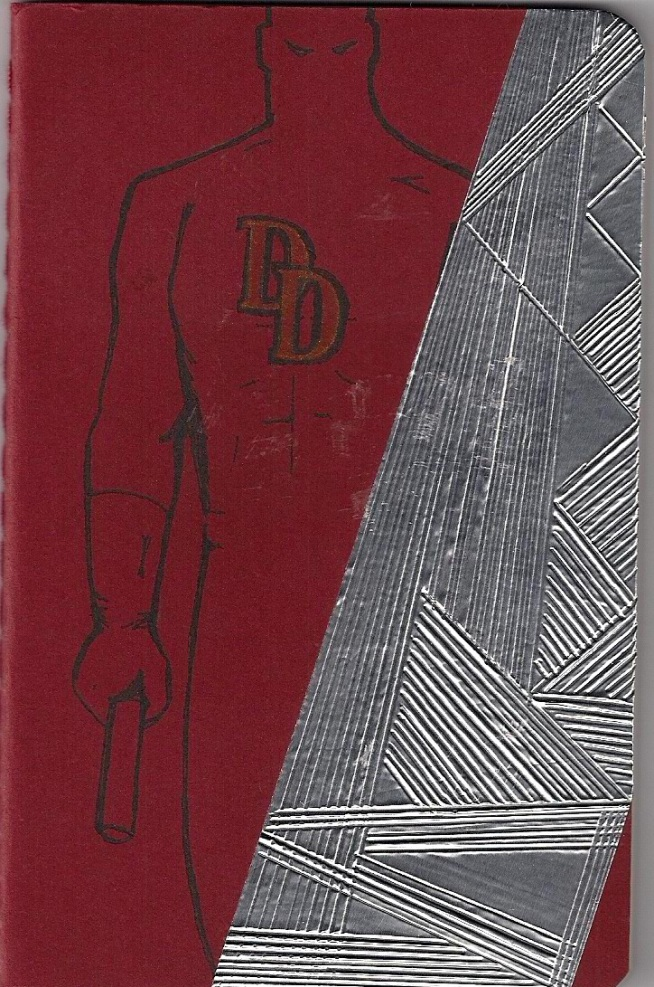 Red Moleskine notebook with DD drawing by me, and embossed metal tape panel